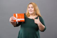 Vrolijke positieve vrouw die op de giftdoos richten stock foto's