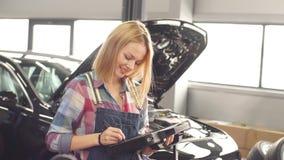 Vrolijke positieve vrouwelijke werktuigkundige die met digitale tablet camera bekijken stock videobeelden