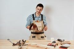 Vrolijke prettige gebaarde schrijnwerker aan het werk op zijn workshop royalty-vrije stock afbeeldingen