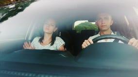 Vrolijke reis in de auto De vrienden gaan naar de auto, zingen en dansen Mening door windscherm