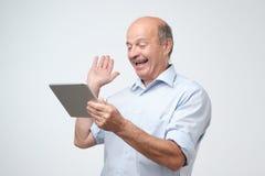 Vrolijke rijpe Europese mens die met zijn computer van de vrienden online gebruikende tablet babbelen royalty-vrije stock afbeeldingen