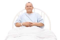 Vrolijke rijpe patiënt die in een het ziekenhuisbed liggen Stock Foto's