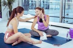 Vrolijke rijpe vrouw die aan yogatrainer luisteren stock foto