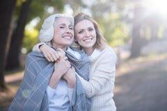 Vrolijke rijpe vrouw die verouderde ouder in openlucht omvatten met deken royalty-vrije stock afbeeldingen