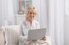 Vrolijke rijpe vrouw die Web zoeken royalty-vrije stock foto's