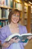Vrolijke rijpe vrouwelijke bibliothecaris die houdend een geopend boek stellen stock fotografie