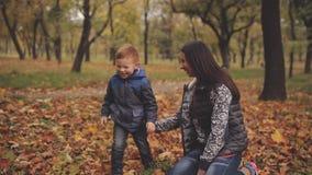 Vrolijke roodharig weinig jongen met zijn moeder compre werpt op gele bladeren in de herfstpark stock video