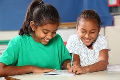 Vrolijke schoolmeisjes die in klasse samen leren Stock Foto
