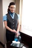 Vrolijke serveerster het openen fles van drank Stock Foto