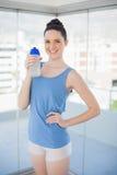 Vrolijke slanke vrouw die plastic fles houdt Stock Afbeeldingen