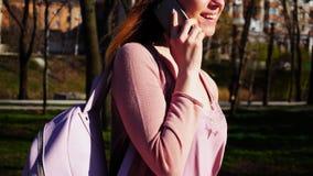 Vrolijke student die in park lopen en door smartphone spreken r Royalty-vrije Stock Afbeeldingen
