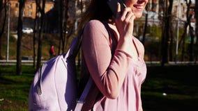 Vrolijke student die in park lopen en door smartphone spreken r Royalty-vrije Stock Fotografie