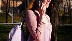 Vrolijke student die in park lopen en door smartphone spreken r Stock Afbeeldingen