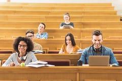 Vrolijke studenten die in lezingszaal bestuderen royalty-vrije stock afbeelding