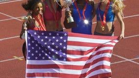 Vrolijke teammates die aan stormachtig applaus die van hun ventilators springen, trofeeën houden stock footage