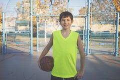 Vrolijke tiener die een basketbal op het hof houden stock foto's