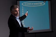 Vrolijke trainer die op het scherm met presentatie richten Royalty-vrije Stock Afbeeldingen