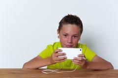 Vrolijke tween jongen die zijn smatrphone gebruiken Royalty-vrije Stock Foto's