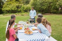 Vrolijke uitgebreide familie lettende op vader bij de barbecue stock fotografie
