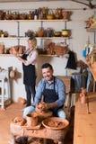 Vrolijke vakman die pot maken die aardewerkwiel gebruiken Royalty-vrije Stock Foto's