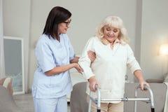 Vrolijke verpleegster die oudere vrouw behandelen stock foto