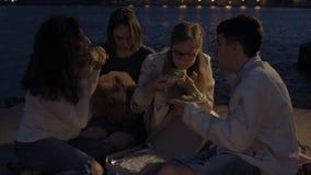 Vrolijke vrienden bij een partij die pizza eten stock videobeelden