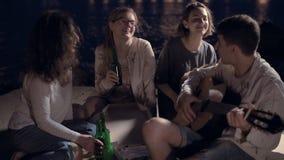 Vrolijke vrienden bij een partij die pizza eten, drinkend bier en het spelen gitaar stock video
