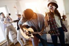 Vrolijke vrienden die partij samen en het spelen instrumenten hebben stock fotografie