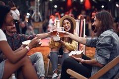 Vrolijke vrienden die van dranken en maaltijd genieten tijdens openluchtmuziekoverleg stock afbeelding