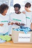 Vrolijke vrijwilligers die een tabletpc bekijken Stock Foto
