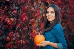 Vrolijke Vrouw in Autumn Leaves Decor Holding een Pompoen royalty-vrije stock afbeelding