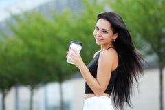 Vrolijke vrouw in de straat het drinken ochtendkoffie in zonneschijn stock foto's