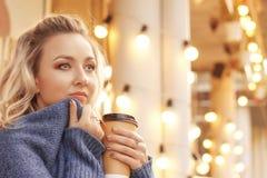 Vrolijke vrouw in de straat het drinken ochtendkoffie in zonneschijnlicht Stock Fotografie