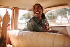 Vrolijke vrouw die door auto met vrienden reizen stock fotografie