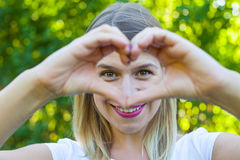 Vrolijke vrouw die een hartsymbool met handen tonen Royalty-vrije Stock Foto's