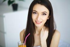 Vrolijke vrouw die een jus d'orangezitting op haar bed drinken Royalty-vrije Stock Fotografie
