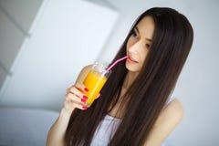 Vrolijke vrouw die een jus d'orangezitting op haar bed drinken bij ho Royalty-vrije Stock Foto