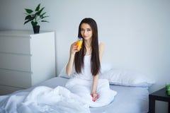 Vrolijke vrouw die een jus d'orangezitting op haar bed drinken bij ho Royalty-vrije Stock Afbeeldingen