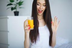 Vrolijke vrouw die een jus d'orangezitting op haar bed drinken bij ho Stock Afbeelding