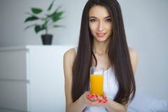 Vrolijke vrouw die een jus d'orangezitting op haar bed drinken bij ho Stock Afbeeldingen