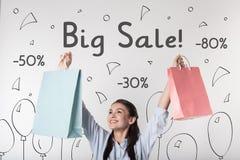Vrolijke vrouw die gelukkig met grote verkoop in wandelgalerij voelen stock foto's
