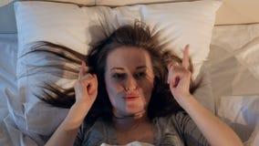 Vrolijke vrouw die in het bed dansen Close-up stock footage