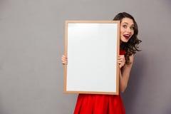 Vrolijke vrouw die lege raad houden Royalty-vrije Stock Afbeeldingen