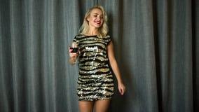 Vrolijke vrouw die met rode wijn dansen stock footage