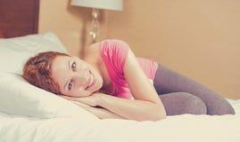 Vrolijke vrouw die op het bed liggen die thuis het rusten dagdromen royalty-vrije stock afbeelding