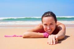 Vrolijke vrouw die op het natte zand ligt Stock Afbeelding