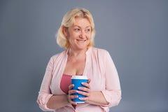 Vrolijke vrouw die op middelbare leeftijd blauwe koffiekop houden stock fotografie