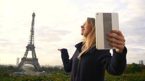 Vrolijke vrouw die videovraag maken door tablet met de Torenachtergrond van Eiffel in langzame motie stock videobeelden