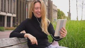 Vrolijke vrouw die videovraag met in oortelefoons en tablet maken, die op bank in park zitten stock video