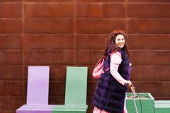 Vrolijke vrouw in een roze kleding en een purpere bontkaap die een autoped berijden stock afbeelding